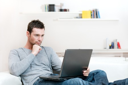 absorbed: Young man working absorbed on laptop at home copy space Stock Photo