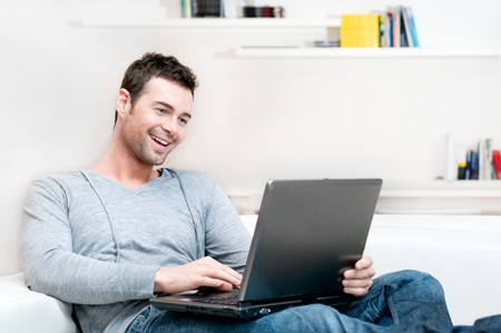 fun at work: Smiling young man working on laptop at home copy space Stock Photo
