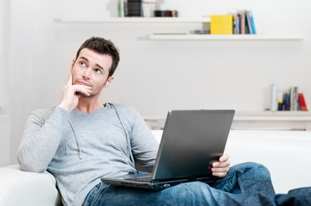 doubtful: Doubtful young man looking up while working on laptop at home