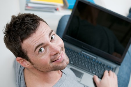 Smiling young man looking back at camera while working on laptop at home photo