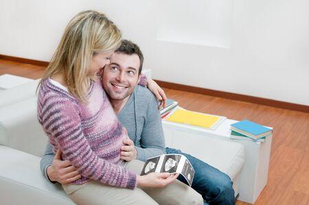 sonograma: Amantes de la pareja joven embarazada sonriente y sosteniendo un sonograma de su nuevo beb�