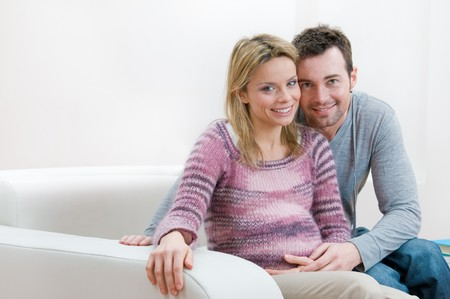 Young smiling pregnant couple looking at caemera with copy space photo
