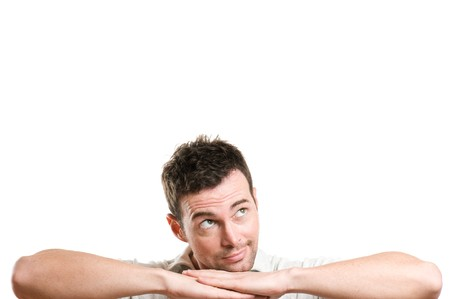 man thinking: Jeune homme de sourire imagine et r�ver regardant espace de la copie de votre texte, isol� sur fond blanc