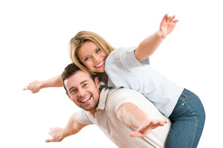 Young beautiful smiling couple having fun together with piggyback and arms outstretched isolated on white background photo