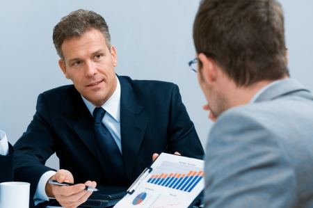 staff meeting: Mature businessman showing growing chart in a meeting discussion at office