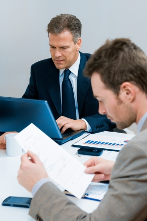 Mature businessman typing on his laptop during a business meeting in office Stock Photo - 8235770