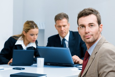 Satisfied confident businessman looking at camera with colleagues in the office Stock Photo - 8235766
