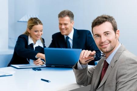 empresario: Sonriendo a satisfecho empresario mirando la c�mara con sus colegas en el fondo durante una reuni�n en la Oficina