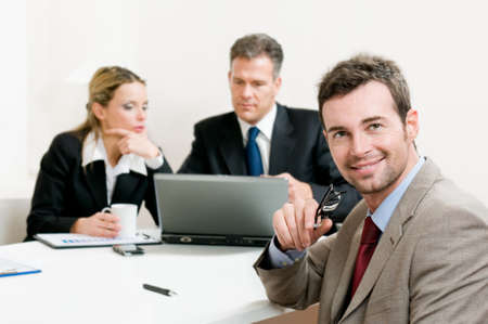Smiling satisfied businessman looking at camera with his colleagues in the background during a meeting in the office Stock Photo - 8235755