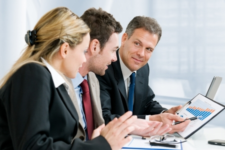 Satisfied senior businessman showing growing chart at his happy colleagues in office Stock Photo - 8235760