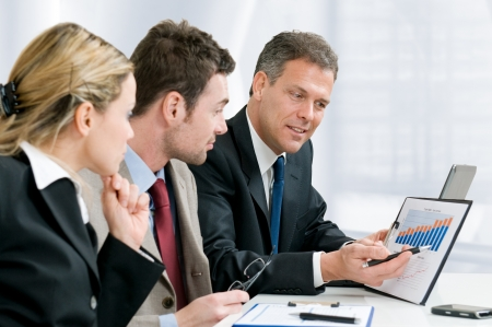 Satisfied senior businessman showing growing chart at his happy colleagues in modern office Stock Photo - 8235732