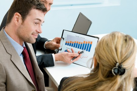 Mature businessman showing growing chart to colleagues in a meeting discussion at office photo