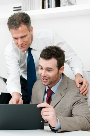 satisfied: Mature manager looking at the work of his young colleague during a meeting in office Stock Photo