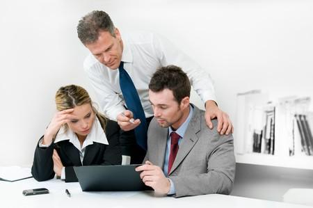 trabajando duro: Compa�eros de negocio trabajando juntos durante una reuni�n en la Oficina