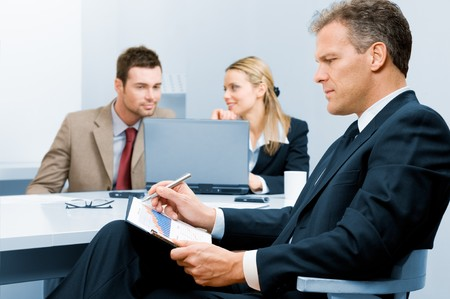 Pensive absorbed mature businessman working on growing chart with colleagues in background photo