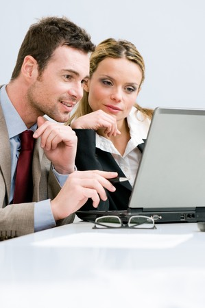 Business colleagues looking and working on laptop in office, vertical copy space photo
