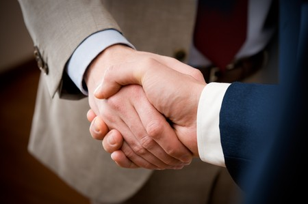 businessmen shaking hands: Two professional businessman giving handshake in the office, closeup selective focus