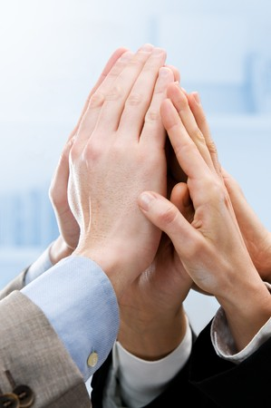 high spirits: Group of hands raised up for an high five in the office. Symbol of teamwork, victory and success