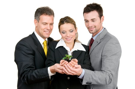 Business team holding a fresh new plant on palm, symbol of green, new and growing business photo