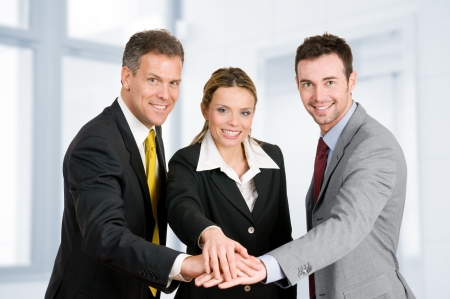 teamwork together: Happy smiling business team holding hands in a heap, good teamwork job