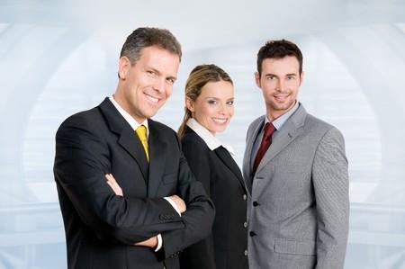 Drie gelukkige zakelijke collega's staan bij elkaar en kijken naar de camera in hun moderne kantoor