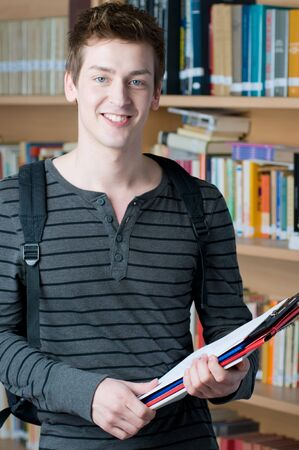 Happy young student holding books in a college library photo
