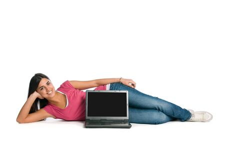 Happy young beautiful lady laying down with laptop and blank screen for your text, isolated on white background
