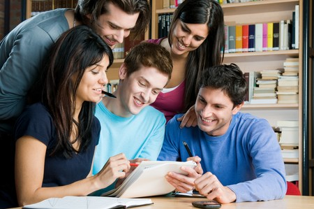 study: Happy group of students studying and working together in a college library