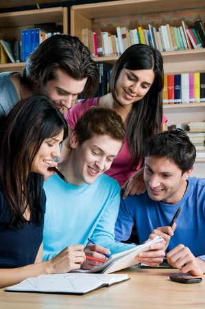 Young group of happy students studying and working together in a college library Stock Photo - 8236170