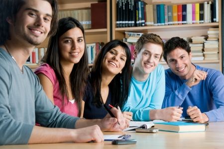 student girl: Happy group of young students studying together in a college library and looking at camera smiling