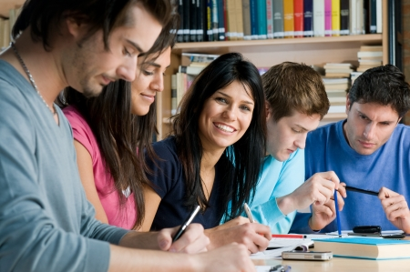 latin students: Group of young students working and studying in a college library, smiling girl looking at camera.