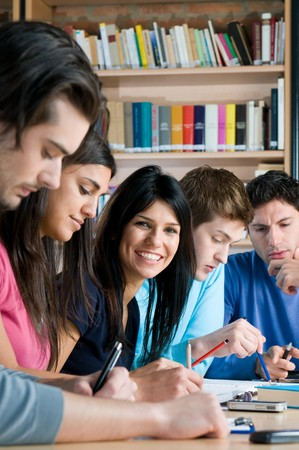 Group of young teenager students working and studying in a college library, smiling girl looking at camera. photo