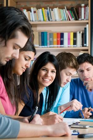 etudiant livre: Groupe de jeune adolescent �tudiants travailler et �tudier dans une biblioth�que de coll�ge, sourire de jeune fille � la recherche � la cam�ra.