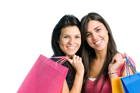 Two beautiful smiling young brunette women doing shopping isolated on white background photo