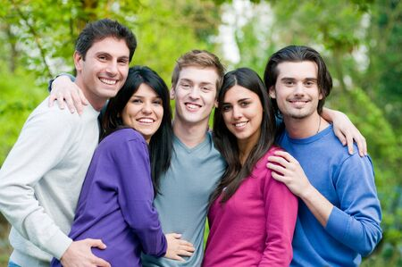 Young group of happy friends embracing and staying together outdoor in the park photo