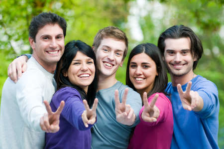 Young group of happy friends showing victory signs together outdoor in the park photo