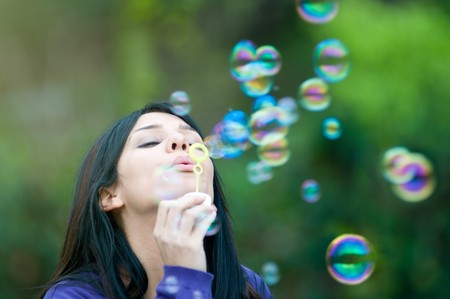 aspirations: Young beautiful girl blowing bubbles in the nature, symbol of hope and aspirations
