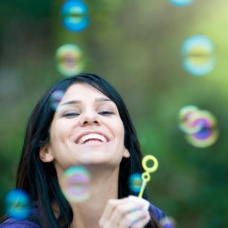 bulles de savon: Belle jeune femme latine souriant et soufflant de bulles en plein air dans la nature