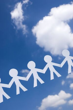 fraternit�: Paper man chain on blue sky with white clouds. Symbol of unity, brotherhood and teamwork