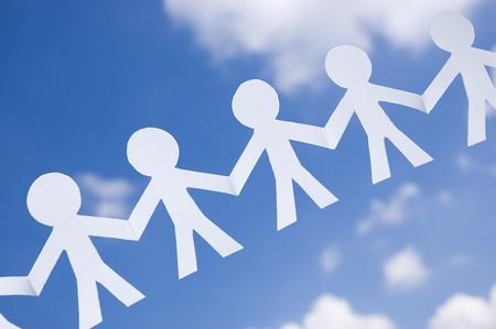 fraternidad: Cadena de hombre de papel en un cielo azul con nubes blancas. S�mbolo de la unidad, la fraternidad y el trabajo en equipo.