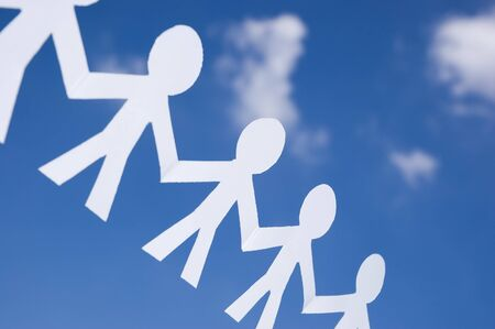 fraternidad: Cadena de hombre de papel en un cielo azul con nubes blancas. S�mbolo de la unidad, la fraternidad y el trabajo en equipo  Foto de archivo
