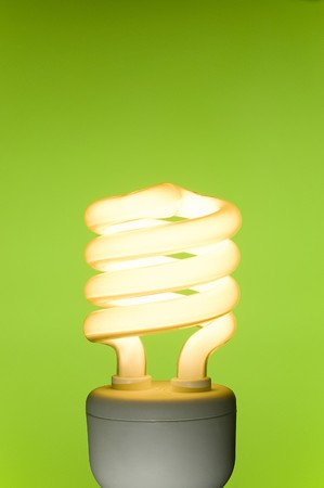 Energy saving fluorescent light bulb on green background. Space for text. photo