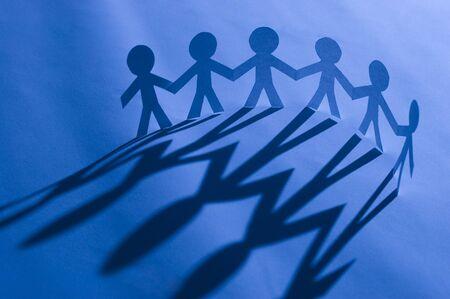 fraternidad: Cadena de hombre de papel aferr�ndose a manos de azul. S�mbolo de la unidad, la fraternidad y el trabajo en equipo