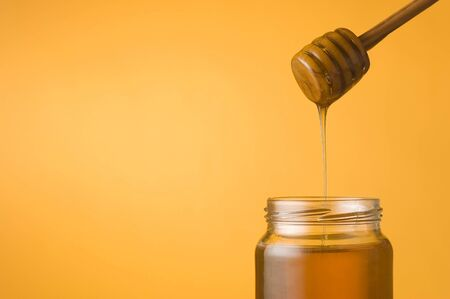 golden pot: Honey falling from a dipper into a jar on orange background. Space for text