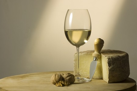 white wine glass: Cutting board with genuine Italian food. White wine glass, ripe hard cheese from ewes milk and walnuts. Warm ray of light in the background. Space for text