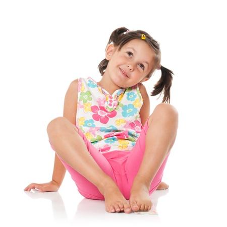 chica pensando: Ni�a sonriente de im�genes y sentada en suelo aislado en fondo blanco