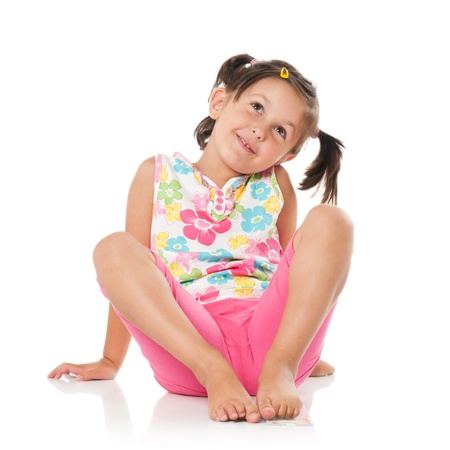 little girl smiling: Smiling little girl imaging and sitting on floor isolated on white background Stock Photo