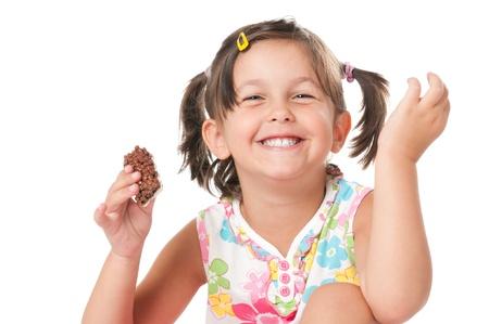greed: Happy joyful little girl eating chocolate bar for snack isolated on white background