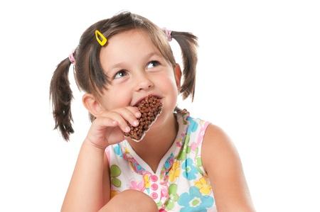 barra de cereal: Little girl comer cereales barra para refrigerio aislado sobre fondo blanco
