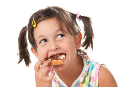 Happy little girl bite a snack of chocolate spread isolated on white background photo